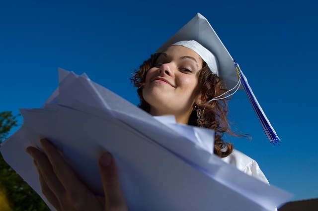 Young graduate woman with heap of papers.